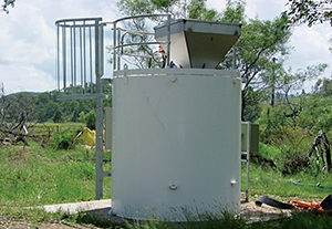 Vertical mixing tank at mine site for mixing and dosing reagents for the treatment of Acid Mine Drainage (AMD) or Acid Rock Drainage (ARD) or other water issues.